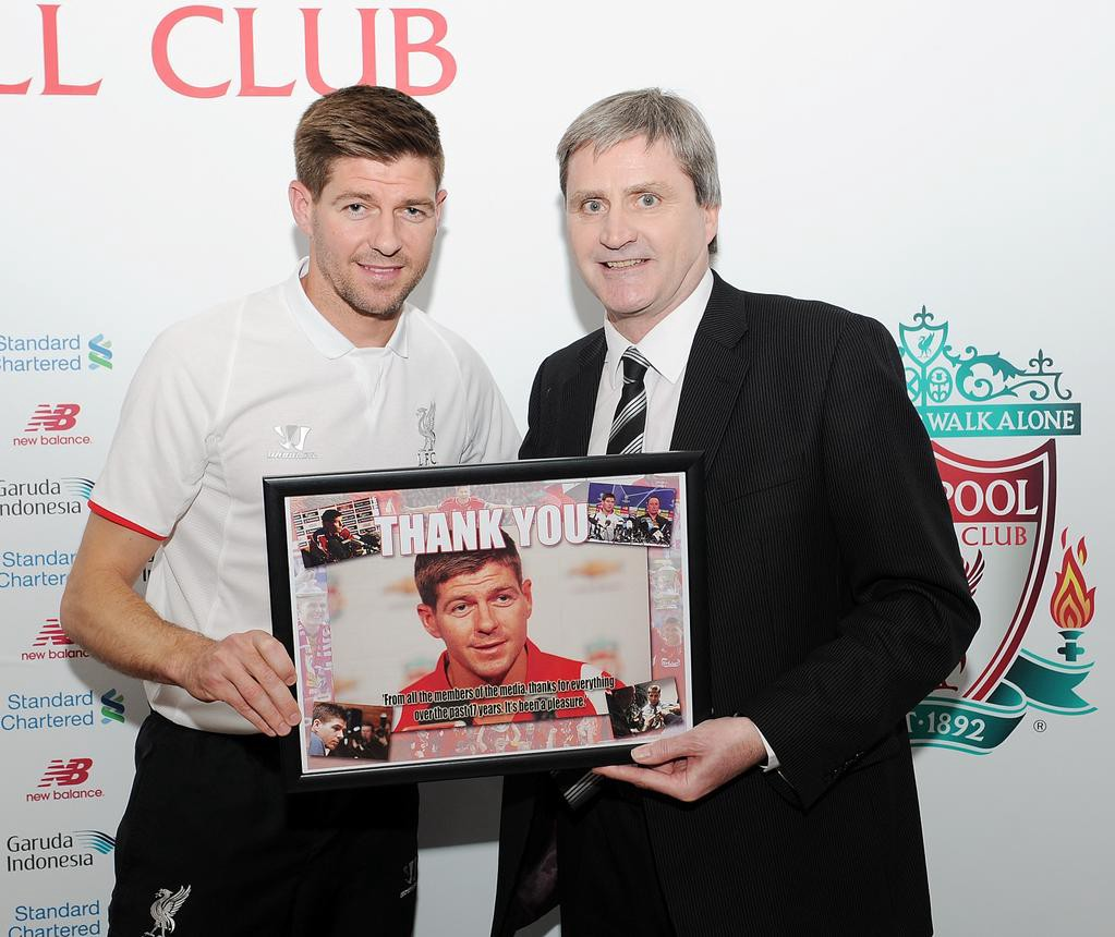 Liverpool Echo editor John Thompson presents Steven Gerrard with a picture created by an 8-year-old using Windows 95 on behalf of the media. (@LFC)