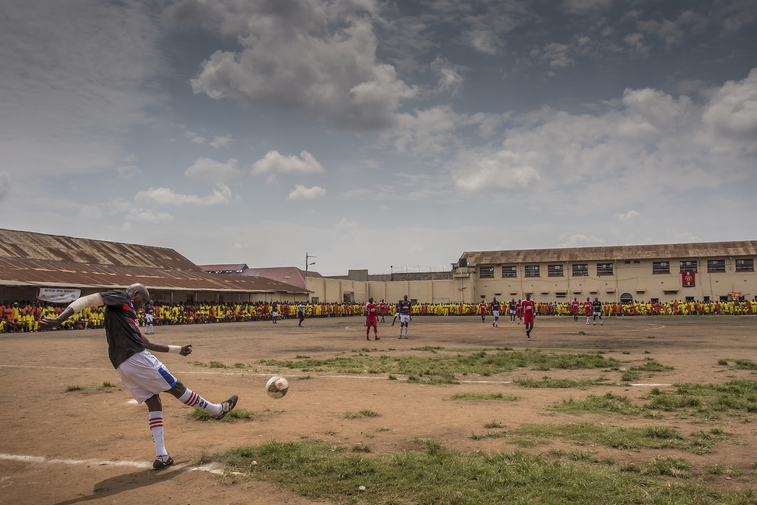 In Luzira Prison, in Kampala, a football league is organized. The teams composed of inmates meet each other throughout the year until a final. The teams are named mainly out of English Premier League clubs: Manchester United, Liverpool, Everton, ... The pitch is the courtyard of the Upper Prison, the most secure place of the Prison large compound. Hundreds of inmates come to support their favorite team. Liverpool in black versus Manchester United in Red. Liverpool will win the match.