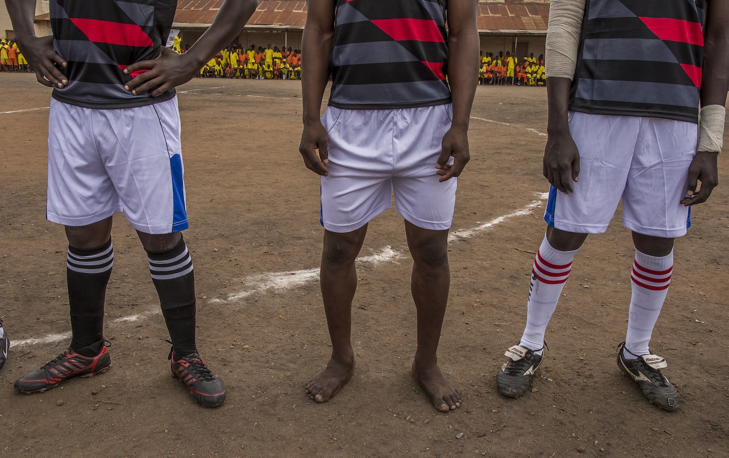 In Luzira Prison, in Kampala, a football league is organized. The teams composed of inmates meet each other throughout the year until a final. The teams are named mainly out of English Premier League clubs: Manchester United, Liverpool, Everton, ... The pitch is the courtyard of the Upper Prison, the most secure place of the Prison large compound. Hundreds of inmates come to support their favorite team. A Liverpool player plays the final barefoot.